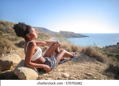 Girl relaxing on a cliff, looking the sea
