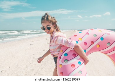 Girl relaxing on donut lilo on the beach. Playing with inflatable ring. Summer holiday idyllic on a tropical island.