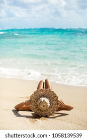 Girl relaxing on a Hawaii beach with a big hat
