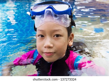 Girl relaxing on the side of a swimming pool wearing goggles and snorkel