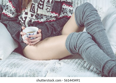 Girl is relaxing on the sofa with tea, winter cozy concept