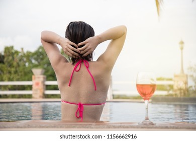 Girl relaxing at the pool.Asian young female person enjoying in pool spa at hotel resort in an exotic paradise getaway.