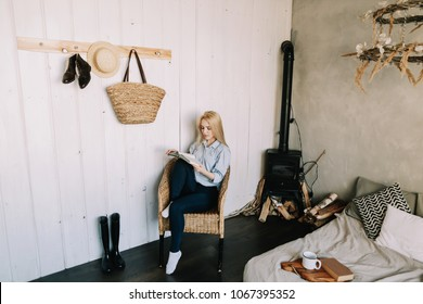 Girl relaxing and reading book in loft living room with white walls bedroom. Young woman chilling at home in comfortable chair. Atmospheric hygge style