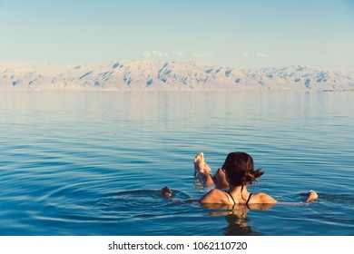 Girl is relaxing and swimming in the water of the Dead Sea in Israel