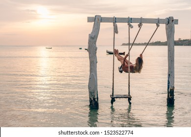 Girl relaxing in swings at paradise island. Dreamy evening on sunset beach.