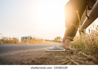 Girl remove casual shoes near road. Because her painful foot.