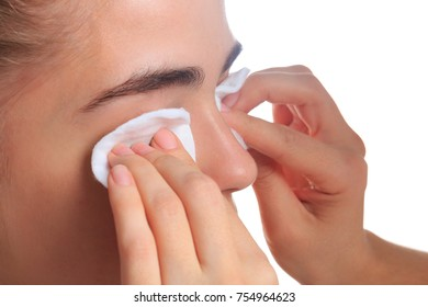 The girl is removed makeup by the closeup of a sponge on a white isolated background