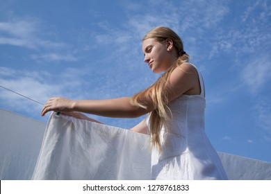 Girl removes dry sheet from clothesline. Drying clean laundry in rope outdoors. View from below