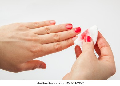 The girl removes the nail polish with cotton wool. Cleaning nails from polish
