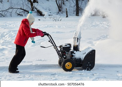 Girl removes snow with gas snow thrower at winter day.