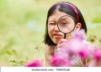 Girl as researcher looks through magnyfing glass with curiosity