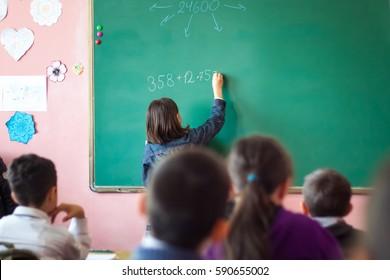 girl resolves mathematical task on board.