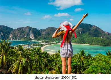 The girl at the resort in a dress and hat on the background of the bays of the island of Phi Phi