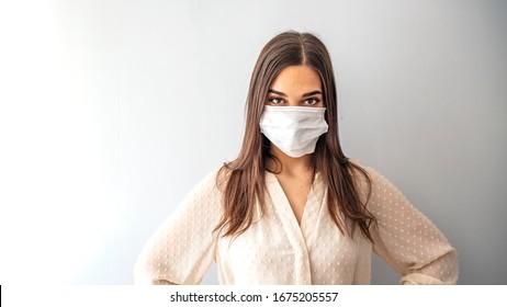 Girl in respiratory mask. Masked woman looks at camera. Cold, flu, virus, tonsillitis, respiratory disease, quarantine, epidemic concept. Beautiful caucasian young woman with disposable face mask