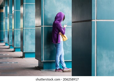a girl rest side by the pillar and playing her phone