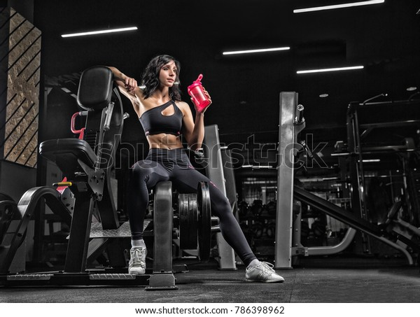 The girl is resting after fitness classes in the gym on a dark background.