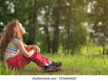 Girl resting in the morning in the park. She put her face to the sun, closed her eyes and feeds energy of nature, dreams, listens to silence.