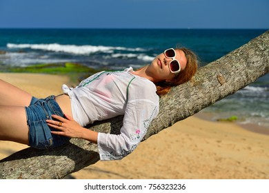 The girl is resting on the palm on the beach