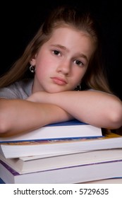 A girl resting on a stack of thick text books, looking overwhelmed.