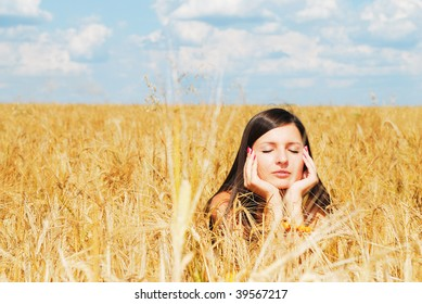 Girl resting on wheat field