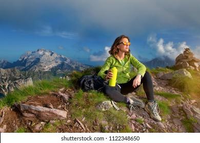 A girl rests after climbing the top of a mountain. He drinks from his borrazzia and observes the sunset