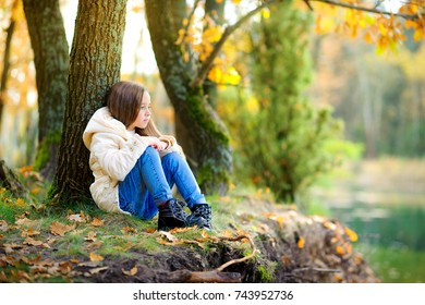 a girl rests in a beautiful park, sits on the shore of a lake and dreams