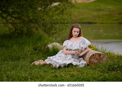 The girl rests by the lake leaning on the old log