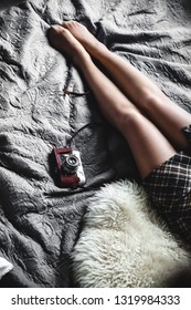 A girl rests in a gray bed with an old camera. Fashion, style, vintage