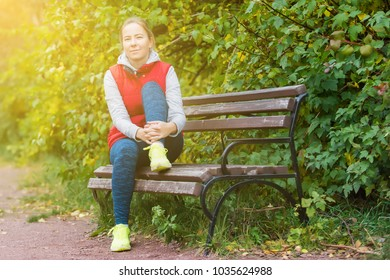the girl rests on the bench after jogging