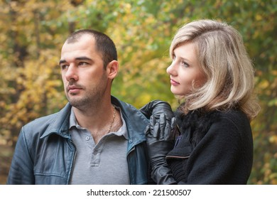 Girl rests on the shoulder of a young man in autumn park