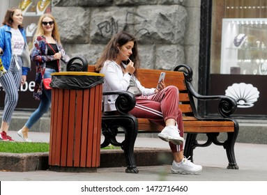 a girl rests and use Apple iphone smarthphone sitting on a bench in Kiev, Ukraine, 1 August 2019.