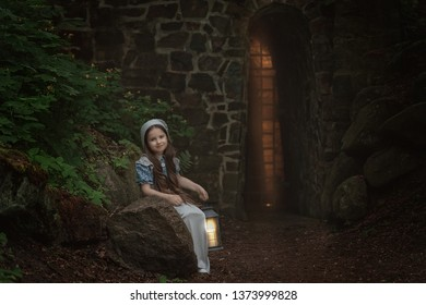 A girl in retro clothes stands with a lantern near the fortress wall.