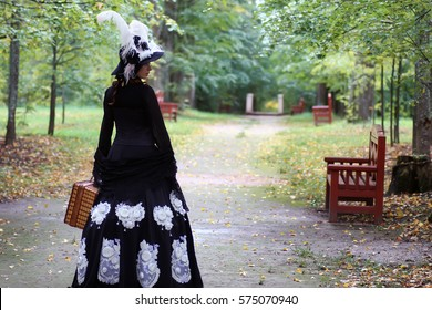 girl in retro dress 18th century with valise in park