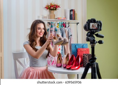 Girl reviews adorable pump shoes. Fashion blogger making a video using a camera with a tripod.