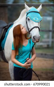Girl rider and her horse to rest near the stable after riding. A girl kisses a horse