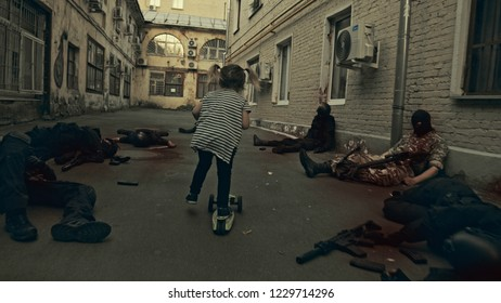 The girl rides between the corpses of the military.