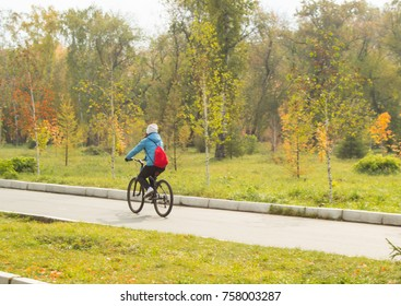 A girl rides a Bicycle in a city Park in autumn.