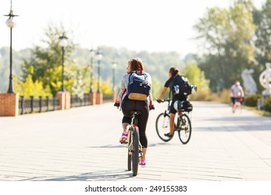 Girl rides a bicycle. Cycling. Road for cyclists. A woman riding a bicycle on a background of blurred silhouettes of other cyclists. Walk on a bicycle in the nature park on the road. Active lifestyle