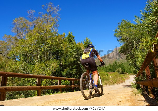 Girl rides a bike in mountains. Shot in August in Jonkershoek Nature Reserve, Stellenbosch, Western Cape, South Africa.
