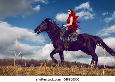 girl rides on a horse in red dress developing in the field on sky background with clouds