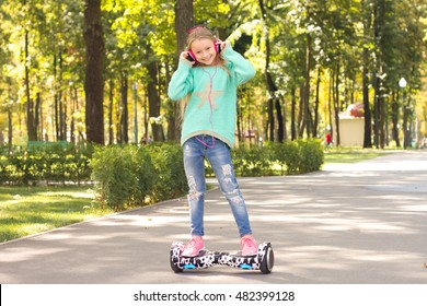 Girl rides on mini segway in the headphones . She is happy and smiling . A popular kind of electric transport
