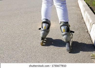 Girl rides on roller skates rides on the asphalt.