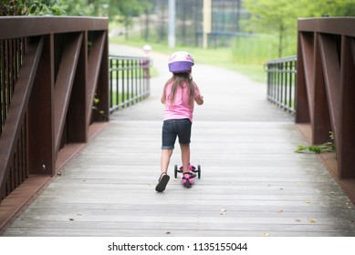 Girl riding away across bridge on scooter