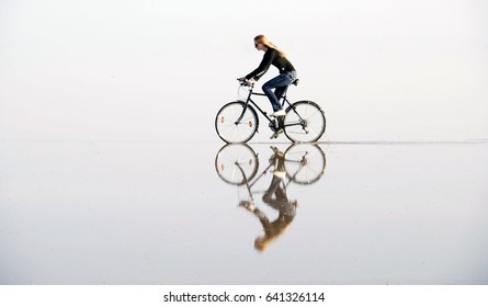 A girl riding a bicycle by water, that creates a bewitching mirror illusion.