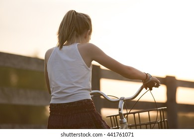 Girl riding a bicycle in the country.