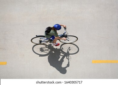 Girl riding a bicycle on a bike path taken from above
