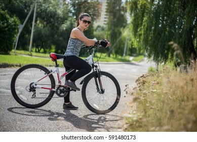 A girl riding a bicycle in a park for sports