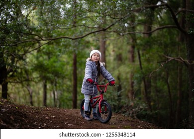 Girl riding a bicycle in the woods