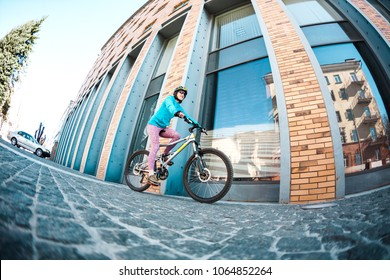the girl is riding a bike around the city. Bicycle rental in the city. fisheye lens.
