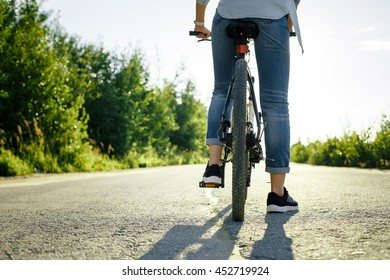 Girl riding a bike in the summer at sunset